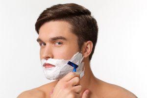 カミソリでひげを剃る男性