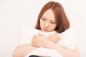 枕を抱えて下を向く女性