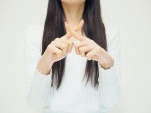 手でバツ印を表現する女性