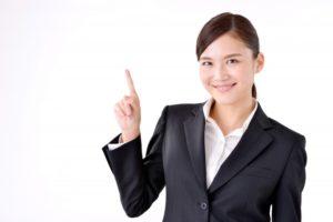 人差し指を立てて微笑んでいるスーツ姿の女性