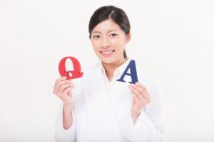 QとAを手に持っている白衣の女性