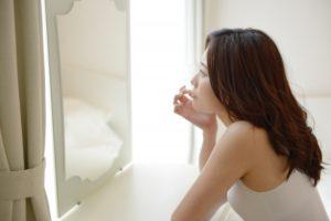 鏡を見ながら口元を気にする女性