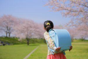桜の木の下でランドセルを背負っている女の子