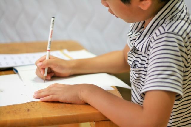机の上で勉強をする男の子