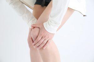 膝を手で抱えている女性
