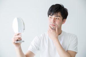 手鏡をもって髭を気にする体毛が濃い男性