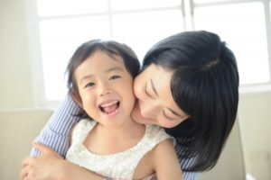笑顔の小さな女の子とそれを優しく抱きしめる母親