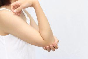 肘に手を当てて悩む女性