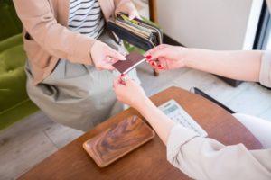 クレジットカードで料金を支払う女性とカードを受け取る従業員女性の手