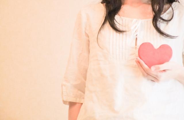 ピンクのハートのオブジェを持つ女性