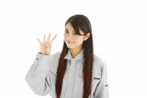 笑顔の女性が片手で数字の4を表している