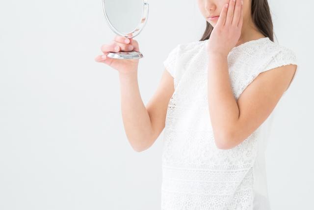真顔で鏡を見る女の子