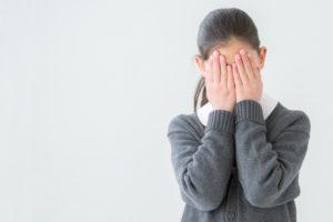 顔を隠す女子学生