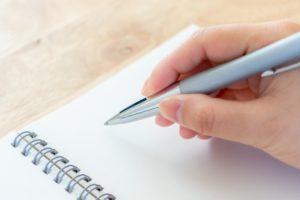 ボールペンでメモと取る女性の手