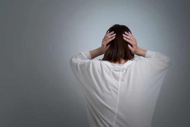 頭を抱えて後ろを向いて落ち込む女性