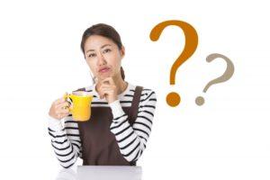 マグカップを持つエプロン姿の女性