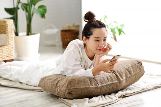 スマートフォンを持つ笑顔の若い女性